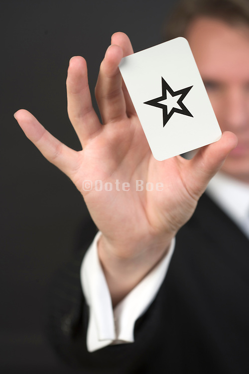 a magician holding a Zenner card with a star sign on it
