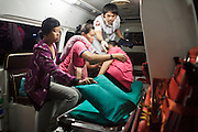 "02 OCTOBER 2009 -- BANGKOK, THAILAND:  A medic helps a woman and her family into an ambulance after she called complaining of a migraine. The medics from Poh Teck Tung took her to a community hospital in Bangkok. The 1,000 plus volunteers of the Poh Teck Tung Foundation are really Bangkok's first responders. Famous because they pick up the dead bodies after murders, traffic accidents, suicides and other unplanned, often violent deaths, they really do much more. Their medics respond to medical emergencies, from minor bumps and scrapes to major trauma. Their technicians respond to building collapses and traffic accidents with heavy equipment and the ""Jaws of Life"" and their divers respond to accidents in the rivers and khlongs of Bangkok. The organization was founded by Chinese immigrants in Bangkok in 1909. Their efforts include a hospital, college tuition for the poor and tsunami relief.   PHOTO BY JACK KURTZ"