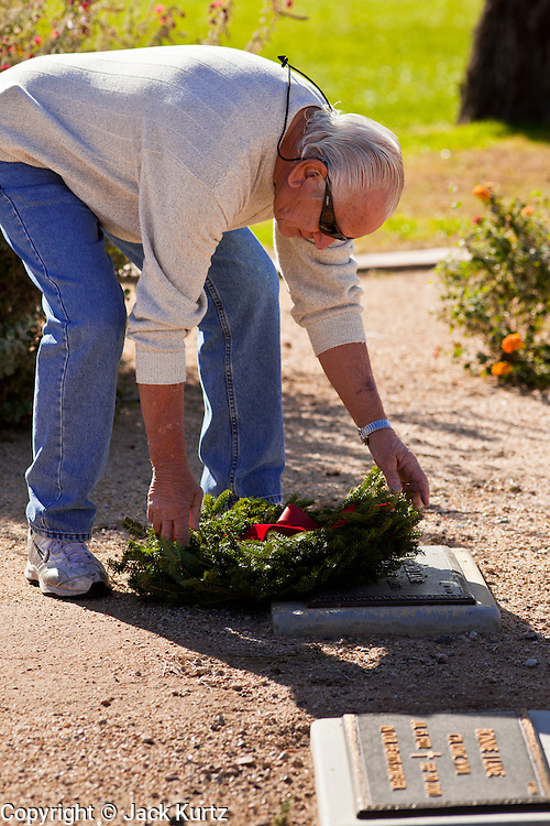 09 DECEMBER 2011 - PHOENIX, AZ:  A man lays a Christmas wreath on a veteran's grave in Phoenix Saturday. Several hundred volunteers and veterans gathered at the National Memorial Cemetery of Arizona in Phoenix Saturday to lay Christmas wreaths on headstones, a tradition started by Wreaths Across America. Wreaths Across America is a nonprofit organization founded to continue and expand the annual wreath laying ceremony at Arlington National Cemetery begun by Maine businessman, Morrill Worcester, in 1992.  PHOTO BY JACK KURTZ