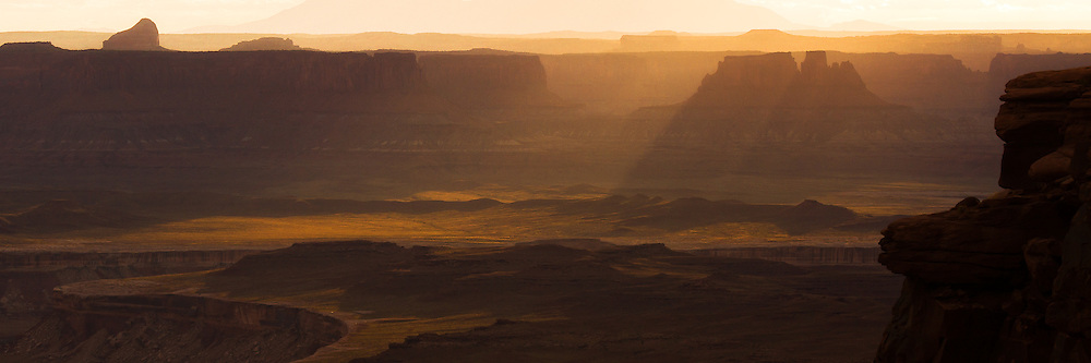 A setting Sun's rays pouring over the edge of the canyon walls near the Green River overlook.