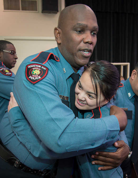 "Minhnguyet ""Nicky"" Tran, right, gets a hug from fellow officer James Wilmore, left, following a swearing-in ceremony for new officers at the Houston ISD Police Department, March 3, 2014."