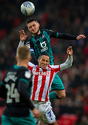 STOKE-ON-TRENT, ENGLAND - Saturday, January 25, 2020: Swansea City's captain Matt Grimes (top) challenges for a header with Stoke City's Tom Ince during the Football League Championship match between Stoke City FC and Swansea City FC at the Britannia Stadium. (Pic by David Rawcliffe/Propaganda)
