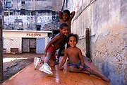 Three little kids in shorts sitting outside a run down housing block in Cuba