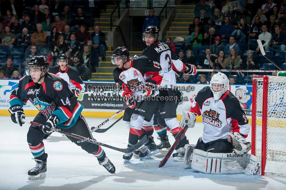 KELOWNA, CANADA - OCTOBER 19: Zach Pochiro #13, Marc McNulty #3 and Ty Edmonds #35 of the Prince George Cougars defend the net against a rebound by Rourke Chartier #14 of the Kelowna Rockets on October 19, 2013 at Prospera Place in Kelowna, British Columbia, Canada.   (Photo by Marissa Baecker/Shoot the Breeze)  ***  Local Caption  ***