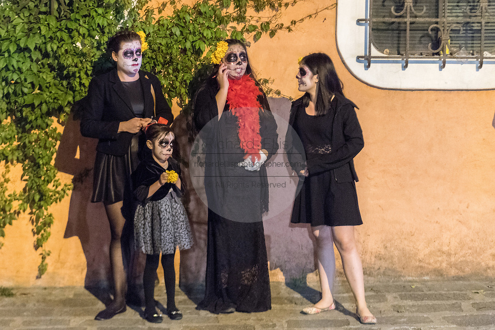 A family costumed as La Calavera Catrina wait for a parade to begin during the Day of the Dead festival November 1, 2016 in San Miguel de Allende, Guanajuato, Mexico. The week-long celebration is a time when Mexicans welcome the dead back to earth for a visit and celebrate life.