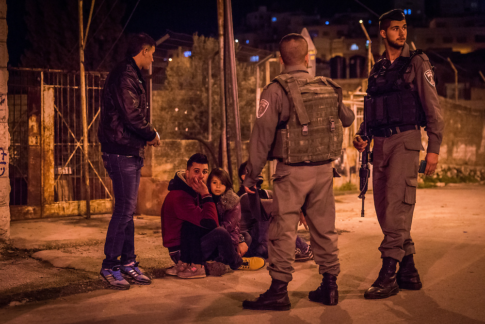 Israeli soldiers detain four Palestinians including a child on their way home after a vigil commemorating the Ibrahimi mosque massacre in Hebron on February 24, 2016.