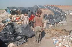 Children and elderly man standing in front of makeshift tents in shanty town on outskirts of Gobindigarh; Punjab; India; next to bundles of cloth and paper waiting to be recycled,