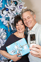 Senior couple taking picture with cell phone in front of Christmas tree