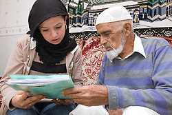 Young woman helping older man to read some paperwork,
