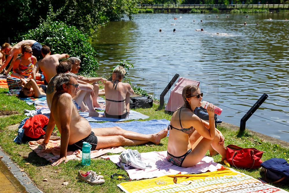 © Licensed to London News Pictures. 05/07/2017. London, UK. People sunbathe in Hampstead Heath Mixed Bathing Pond in north London as temperatures hit 28C degrees on 5 July 2017. Photo credit: Tolga Akmen/LNP