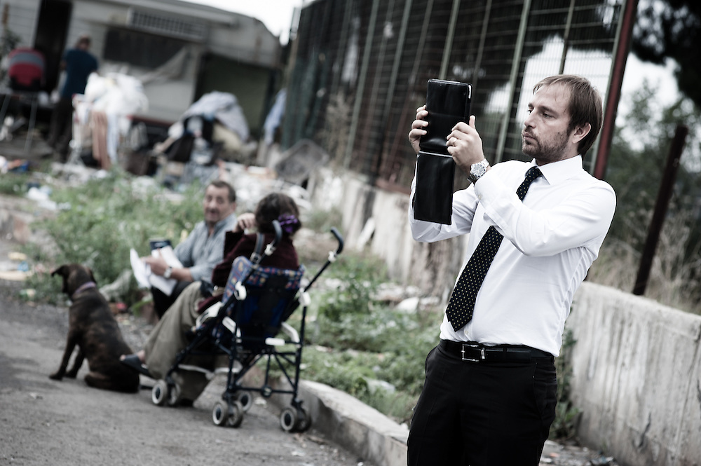 "Rome, Italy - 28 September 2012: Fabrizio Santori, president of the security commission for the city of Rome, takes pictures with his iPad during the Tor de' Cenci camp forced eviction. His comment on the eviction has been ""It is a victory of legality, common sense and of the rights of Roman citizens.[]""Tor de' Cenci has been for years a thorn in the side of thousands of residents who put their trust in the center-right coalition to restore their rights, trampled on in the do-goodery indifference of past city administrations."""