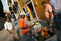 """A man sells coconuts on the street in the """"Old City"""" in Cartagena, a unique travel destination on Colombia's Caribbean coast. (Photo/Scott Dalton)"""