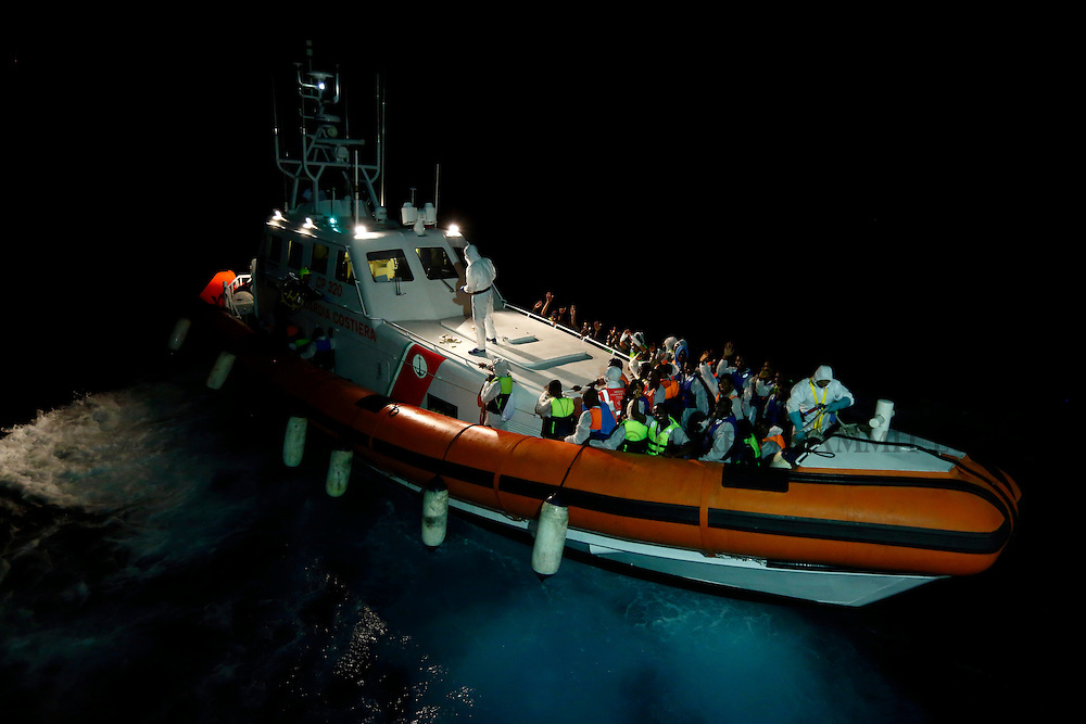 An Italian Coast Guard vessel pulls away from the Migrant Offshore Aid Station (MOAS) ship MV Phoenix after taking on board its rescued migrants between Libya and the Italian island of Lampedusa, August 3, 2015.  Some 118 migrants were rescued by the MOAS ship MV Phoenix from a rubber dinghy around 20 miles (32 kilometres) off the coast of Libya on Monday morning. The Phoenix, manned by personnel from international non-governmental organisations Medecins san Frontiere (MSF) and MOAS, is the first privately funded vessel to operate in the Mediterranean.<br /> REUTERS/Darrin Zammit Lupi <br /> MALTA OUT. NO COMMERCIAL OR EDITORIAL SALES IN MALTA