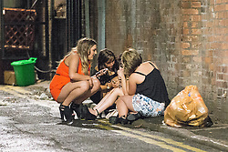 © Licensed to London News Pictures . 01/01/2015 . Manchester , UK . Three women tend to a fourth on the ground in an alley opposite Manchester Town Hall . Revellers usher in the New Year on a night out in Manchester City Centre .  Photo credit : Joel Goodman/LNP