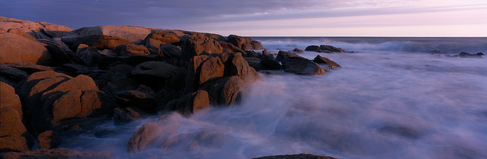 Australia, Victoria, Rocky shoreline meets rolling surf along Bass Strait at sunset in Cape Conran State Reserve