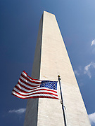 A low-angle view of the Washington Momument on a beautiful day with an American flag flying in front of it.