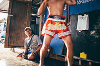 Sompon Samrong watches as his son, Boonsong, limbers up before a fight in Pattaya that night.