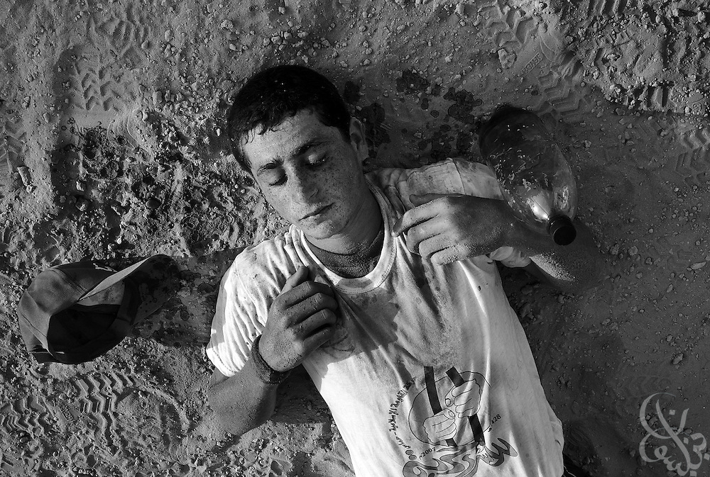 A Palestinian boy lies passed out cold from dehydration during training August 01, 2007 at a HAMAS sponsored summer camp in Gaza City, Gaza. Kids at the camp are given intensive military style training meant to toughen them up, and often endure whippings, smacks of a stick and sand kicked in their eyes by their HAMAS trainers.