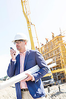 Supervisor using walkie-talkie while holding blueprints at construction site