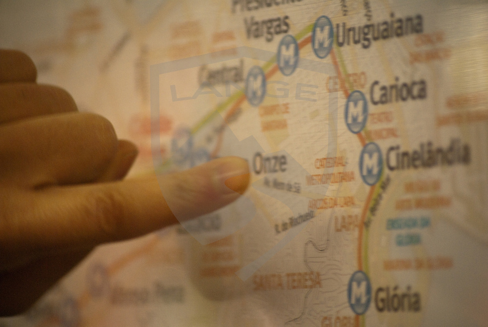 a close up of a hand and finger pointing the way on a map in the rio de janeiro subway system.