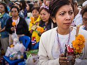 01 JANUARY 2014 - BANGKOK, THAILAND: An anti-government protestor waits to give Buddhist monks milk and flowers during a merit making ceremony Wednesday. Thousands of anti-government protestors are camped out at Democracy Monument in central Bangkok protesting against the government of Yingluck Shinawatra. The protest leader, Suthep Thaugsuban, has called for residents of the Thai capital to rise up against Yingluck. He has promised to shut the city of 12 million down in his final push to overthrow the government. About 100 members of the Thailand's Buddhist clergy visited the protest site Wednesday morning for a special New Year's Day merit making ceremony for the protestors.     PHOTO BY JACK KURTZ