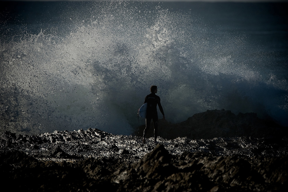 June 3rd, 2011: Surfer waits to jump off the rock as a wave crashes into the rocks at Snapper Rocks on the Gold Coast, Queensland, Australia. Photo by Matt Roberts