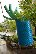 The outstretched hand of Buster Simpson's Beckoning Cistern (2002) manages roof stormwater runoff from the 81 Vine Street Building.  The sculpture was funded by the Seattle Public Utilities 1% for Art Program to support the Growing Vine Street Project, a green street concept developed in the 1990s in Seattle's Belltown district.  The concept of Growing Vine Street is to use biofiltration and other Green Street elements to treat stormwater before it is released directly into Elliott Bay.  This functional sculpture performs flow control and treatment for urban runoff in a visible and demonstrative way, bringing public awareness to the City's water conservation efforts.