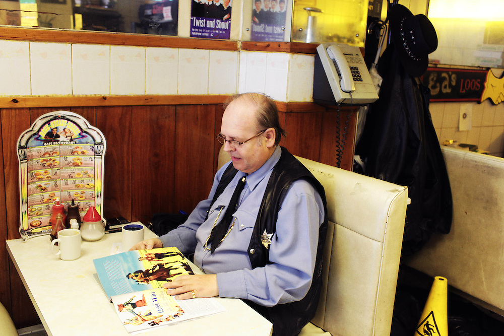 UK. London. Cowboy enthusiast reads his John Wayne magazine at Rock Steady Eddies cafe in south London.