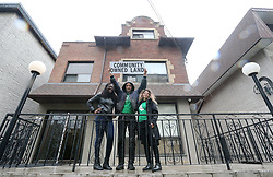 May 1, 2019 - Toronto, ON, Canada - TORONTO, ON- MAY 1  -  Joshua Barndt holds up a sign with Raven Williams and Ana Teresa Portillo on the porch of the 15 unit building for the pilot. An arm of the Parkdale Community Land Trust has, in partnership with the city, purchased and taken over a rooming house in Parkdale. Gord Perks '' The goal of the pilot program was to enable local nonprofit organizations to buy a rooming house before it's sold to someone else and all the tenants get evicted.''  in Toronto. May 1, 2019. Steve Russell/Toronto Star (Credit Image: © Steve Russell/The Toronto Star via ZUMA Wire)