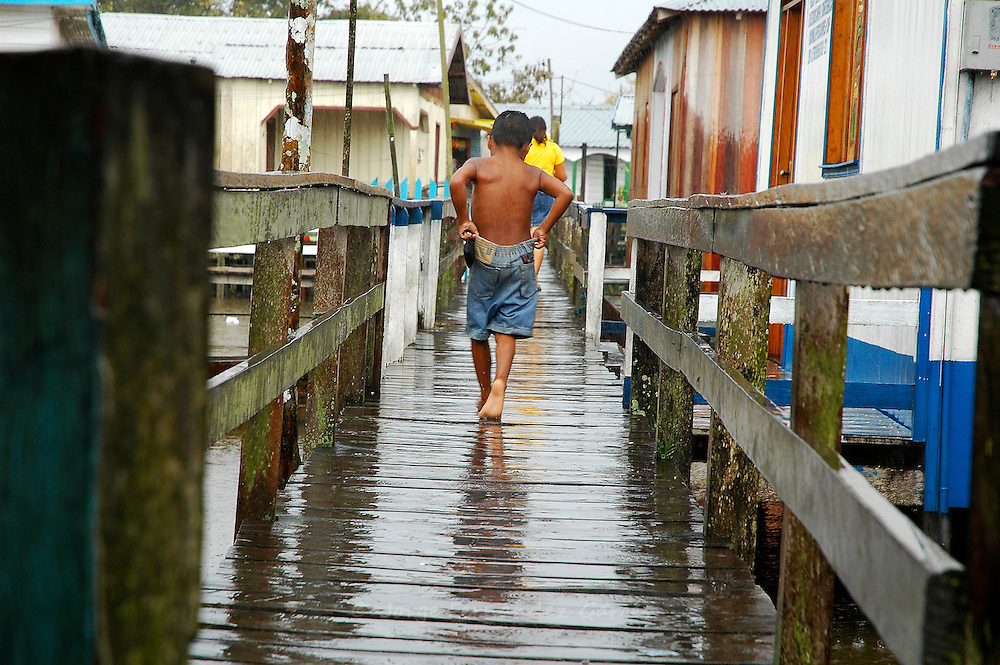 Young boy walking on a boardwalk near Manaos, Brazil