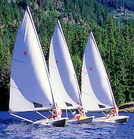Three laser sailboats race on Alta Lake, Whistler, BC Canada.