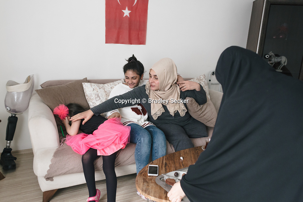 Vahide Şefkatlıoğlu, (2nd from right) at her sister's home with her two daughters, Aisha (right) and Zainab (2nd from left) and niece Ercan (left) in Esenler, Istanbul, Turkey. Vahide's husband was killed by a military tank that injured her and left her an amputee.