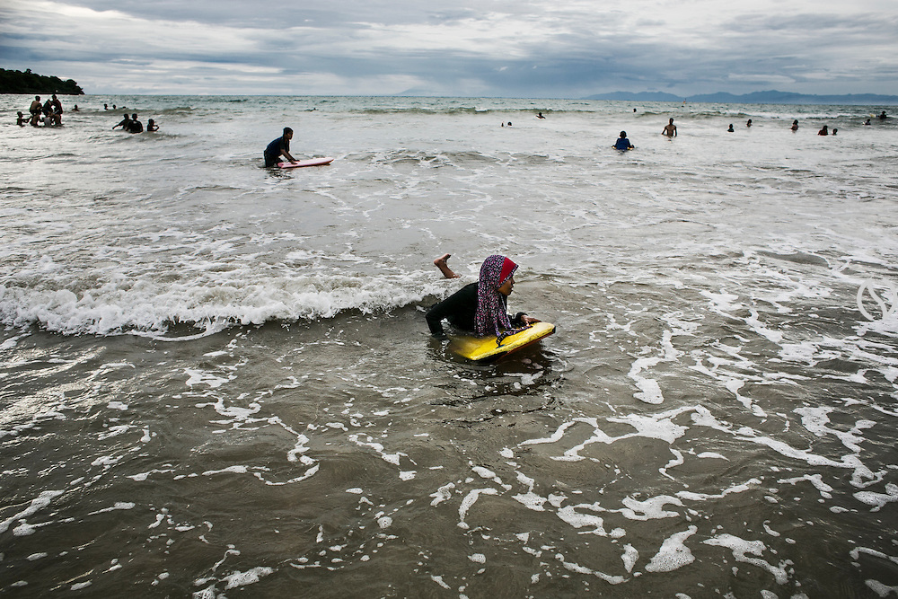 BALI, INDONESIA; APRIL 26, 2015: An Indonesian muslim woman plays bodysurfing at Jimbaran beach on Sunday, April 26, 2015.