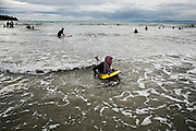 BALI, INDONESIA; APRIL 26, 2015: An Indonesian muslim woman plays bodysurfing at Jimbaran beach on Sunday, April 26, 2015.