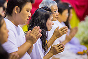 23 OCTOBER 2012 - HAT YAI, SONGKHLA, THAILAND: People pray during a special service on the last day of the Vegetarian Festival at Wat Ta Won Vararum, a Chinese Buddhist temple in Hat Yai. The Vegetarian Festival is celebrated in Thai-Chinese communities throughout Thailand. It is the Thai Buddhist version of the The Nine Emperor Gods Festival, a nine-day Taoist celebration celebrated in the 9th lunar month of the Chinese calendar. For nine days, those who are participating in the festival dress all in white and abstain from eating meat, poultry, seafood, and dairy products. Vendors and proprietors of restaurants indicate that vegetarian food is for sale at their establishments by putting a yellow flag out with Thai characters for meatless written on it in red.   PHOTO BY JACK KURTZ