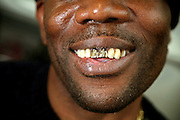 A Yardi prisoner shows off his gold teeth with crosses engraved in them. A Yardi is a type of Jamaican gangster developed from slang.  .HMP Coldingley, Surrey was built in 1969 and is a Category C training prison. Coldingley is focused on the resettlement of prisoners and all prisoners must work a full working week within the prison. Its capacity is 390 prisoners.