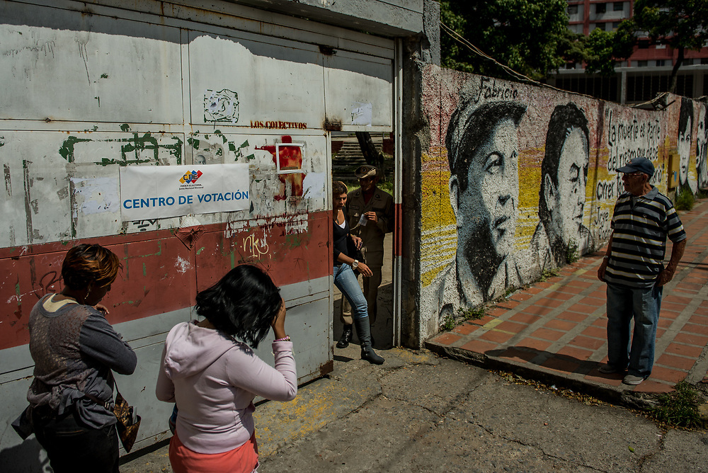 CARACAS, VENEZUELA - JULY 30, 2017:  Only a few dozen voters were present at a polling station at 10am in the 23 de Enero neighborhood - which is infamous for being the most powerful government stronghold in all of Caracas. Lines to vote for the new National Constituent Assembly's candidates were significantly shorter across Caracas than those of the opposition's July 16th symbolic vote against the new assembly. Nonetheless, the government reported on state television that millions had turned out to vote.  Many fear that today's election for a new National Constituent Assembly will turn Venezuela similar to Cuba. Opponents of the government criticize President Maduro for calling for this election - saying the new assembly is a power grab, and will be a puppet of the President - the only candidates on the ballot are government loyalists. Critics also fear the new assembly will turn the country into a dictatorship, re-write the constitution and wipe out the democratically elected and opposition controlled congress. There have been widespread reports of voter intimidation, and of the government threatening state workers and citizens that receive government benefits like subsidized food - who report the government telling them they are obligated to vote, and if they don't, they will lose their jobs and benefits. Thousands have taken to the streets to protest the election in the days leading up to the July 30th vote.  PHOTO: Meridith Kohut for The New York Times