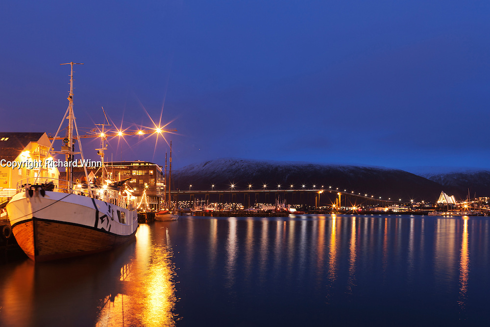View of the harbour area near to the Tromsø Polarmuseet (Polar Museum), with Tromsø bridge lit in the midground and the Arctic Cathedral (Tromsdalen Church) in the background.