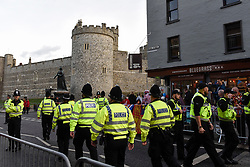 © Licensed to London News Pictures. 12/10/2018. WINDSOR, UK.  Police patrol in front of crowds gathered in Windsor for the royal wedding of Princess Eugenie and Jack Brooksbank.  Princess Eugenie, 28, the younger daughter of the queen's third child Prince Andrew and his ex-wife Sarah Ferguson, the Duchess of York, will marry Jack Brooksbank, a 32-year-old drinks executive, in Windsor Castle before taking part in a short carriage procession through Windsor town.  This is the second royal wedding in Windsor in 2018, Prince Harry married Meghan Markle in May.  Photo credit: Stephen Chung/LNP