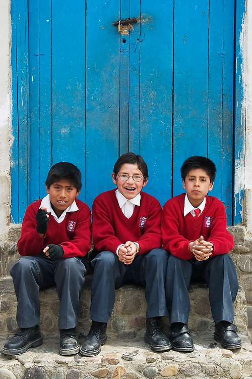 Three boys in red Catholic school uniforms sit together on stairs under a blue door in Paucartambo, Peru.