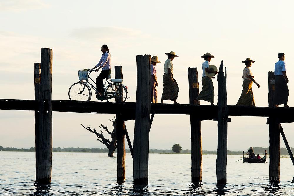 People crossing the U Bein bridge by dusk