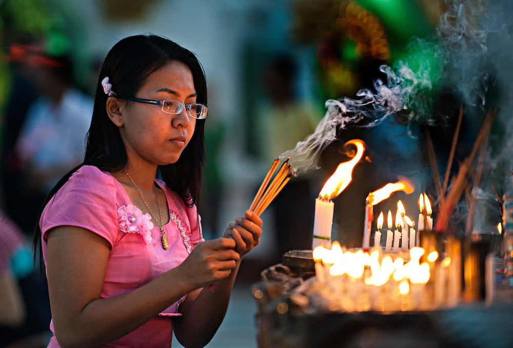 A woman burning incense at the Shwedagon Pagoda in Yangon, Myanmar.