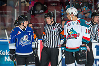 KELOWNA, CANADA - FEBRUARY 12: Referee Mike Campbell stands between Matthew Phillips #11 of the Victoria Royals and Carsen Twarynski #18 of the Kelowna Rockets to discuss a call on February 12, 2018 at Prospera Place in Kelowna, British Columbia, Canada.  (Photo by Marissa Baecker/Shoot the Breeze)  *** Local Caption ***