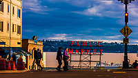 Pedestrians walking in front of the famous Public Market neon sign at the Pike Place Market in Seattle, Washington USA.