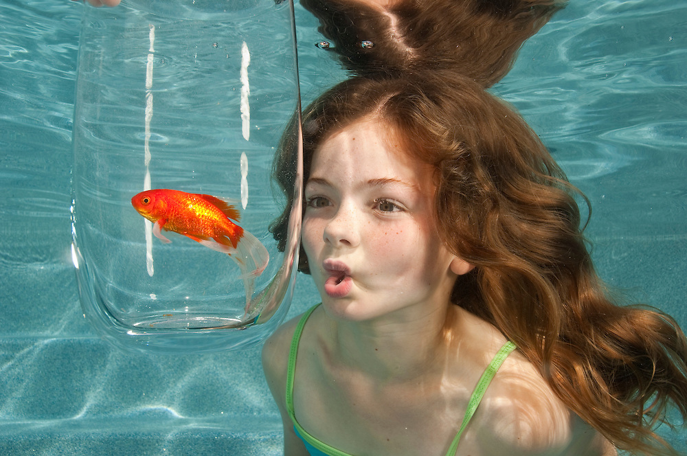 swimming underwater in swimming pool looking at goldfish in glass bowl.