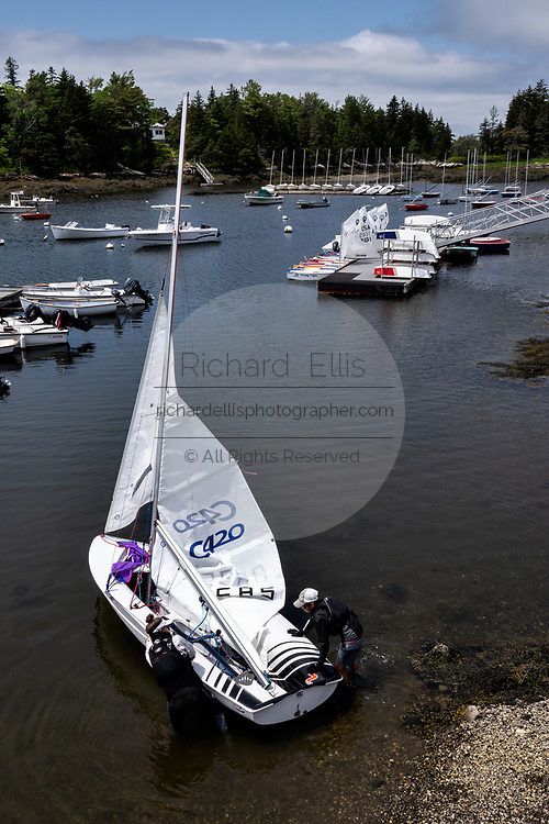 Sailors put in a sailboat at the Southport Yacht Club at Cozy Harbor in Southport, Boothbay Harbor, Maine.