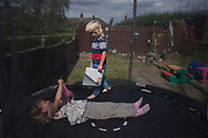 McKenzie (6), Regan (5), read in their trampoline at home in Shefield UK Tuesday, Aug. 12, 2014The D'Arby family is involved in the FAST  (Families and Schools Together) program which encourages parents to read to their children at home.(Elizabeth Dalziel for Save the Children )