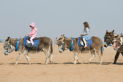 © Licensed to London News Pictures. 10/4/2015. Skegness, Lincolnshire, UK.<br /> People enjoying the warmest day of the year so far in the holiday resort of Skegness. Pictured, the donkey rides were proving popular on a hot sunny day. Photo credit : Dave Warren/LNP
