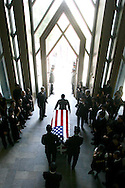 The casket of Army Medic Shin Woo Kim is escorted out of the Sky Rose Chapel during his funeral services Saturday.
