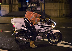 © Licensed to London News Pictures. 13/01/2017. Great Yarmouth, UK. A resident carries sandbanks on a motorbike to his house near the seafront in Great Yarmouth. The Environment Agency has warned residents to prepare for evacuation as as they fear flooding at tonight's high tide. Photo credit: Peter Macdiarmid/LNP